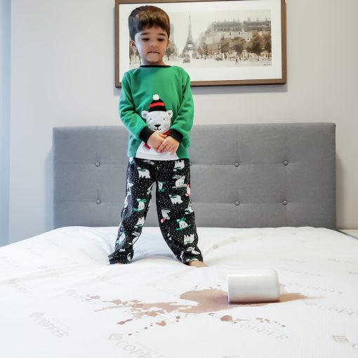 Kid spilling hot cocoa on a Paarizaat Copper Mattress Protector with Kid